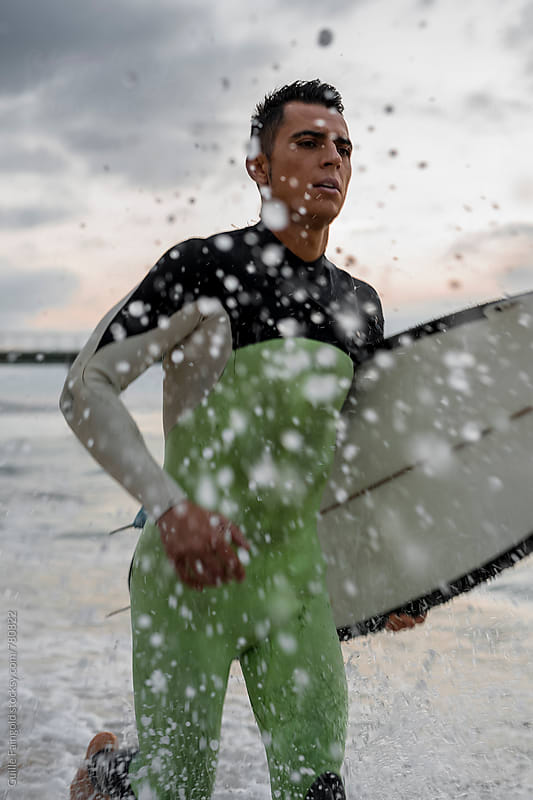 surfer running on the shore by Guille Faingold for Stocksy United