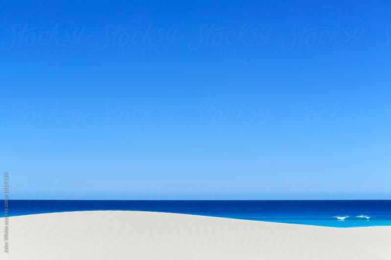 Blue sky the ocean and a sand dune. Eyre Peninsula. by John White for Stocksy United