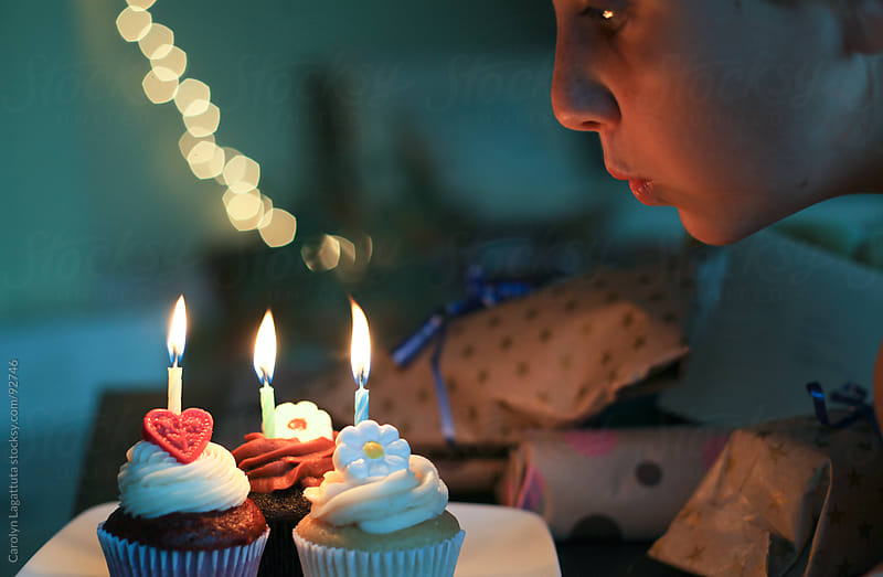 Girl blowing out candles on three cupcakes by Carolyn Lagattuta for Stocksy United