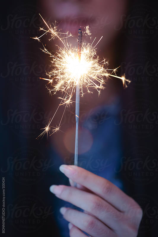 Close up of hands of a woman holding sparkler. by BONNINSTUDIO for Stocksy United