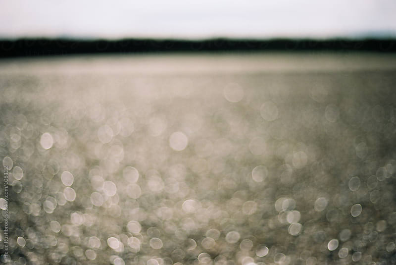 An impressionistic image of water lying on a beach at low tide by Helen Rushbrook for Stocksy United