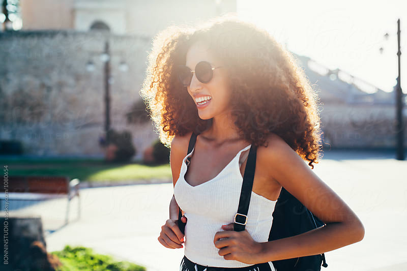 Smiling female tourist visiting a beautiful village on a sunny summer day. by BONNINSTUDIO for Stocksy United
