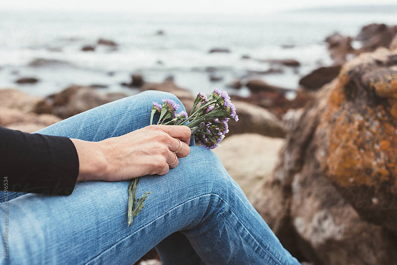 Woman sits on rocks by the ocean holding a small posy of wild flowers in her hand by Jacqui Miller for Stocksy United