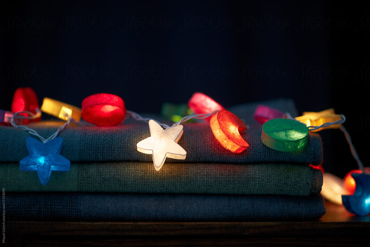 stack of wool blankets with christmas lights on by miquel llonch for stocksy united