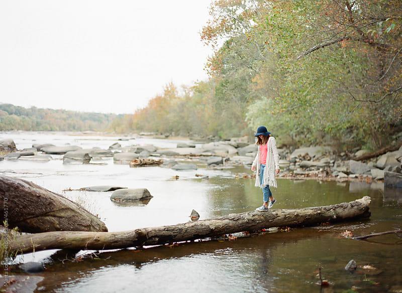 Teen girl walking along a fallen tree across the river by Marta Locklear for Stocksy United