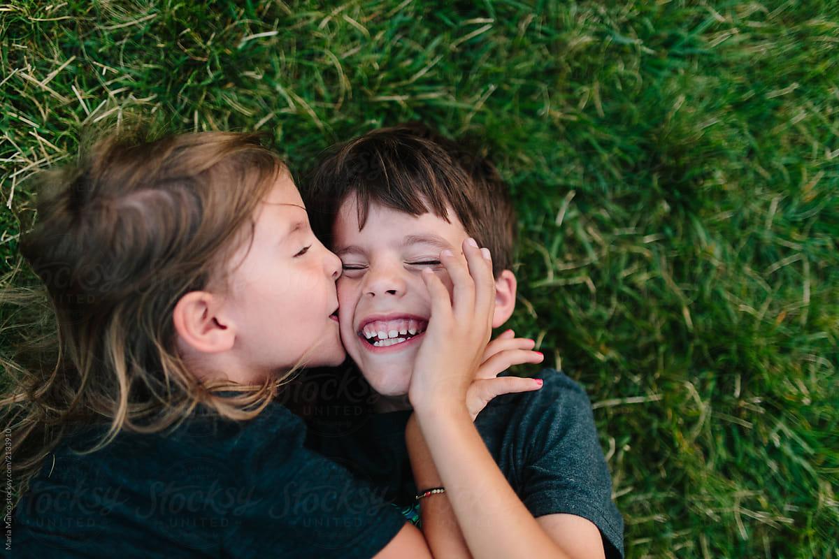 siblings hugging and laughing on sidewalk stocksy united