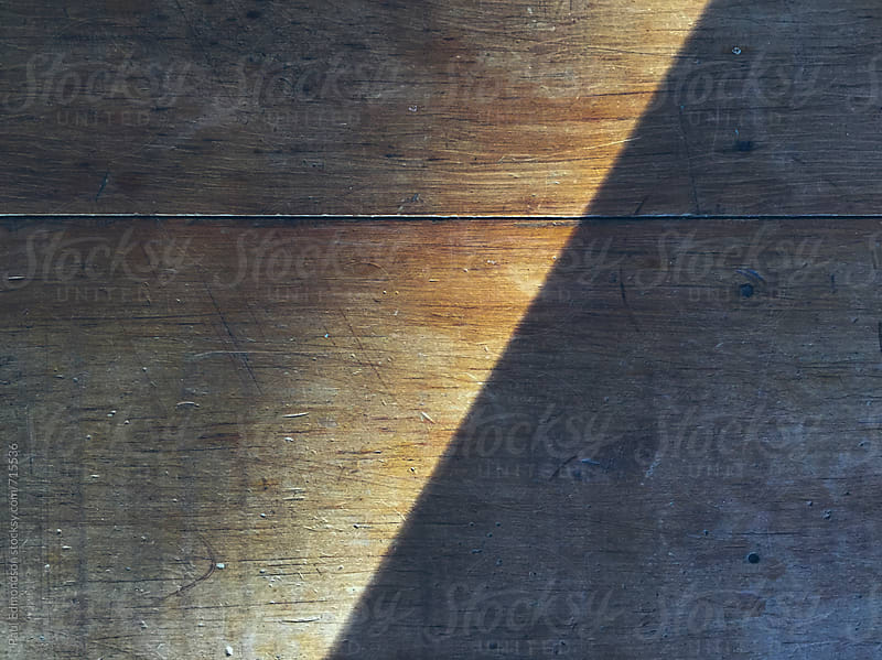 Shadow on worn wood table, close up by Paul Edmondson for Stocksy United