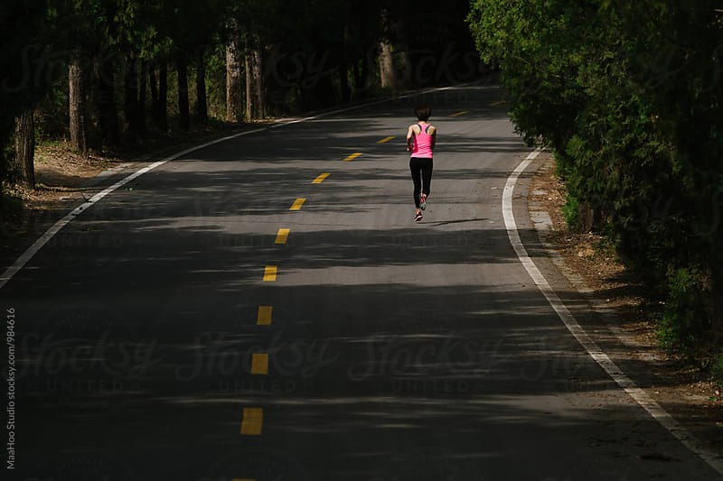 Young woman running on a road by MaaHoo Studio for Stocksy United