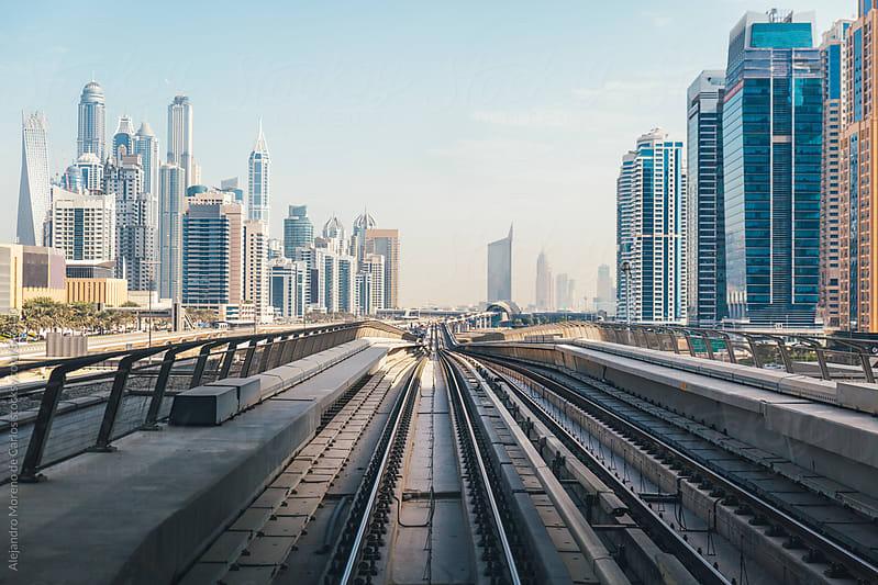 Train tracks and city buildings view in Dubai metro railway network. Dubai, United Arab Emirates by Alejandro Moreno de Carlos for Stocksy United