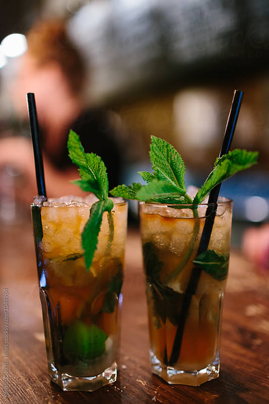 Two tall mojitos sitting at the bar by Kristen Curette Hines for Stocksy United