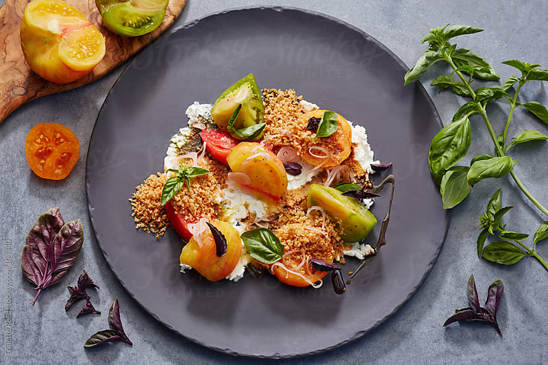 Heirloom tomato salad with burrata cheese, sweet basil saba and pine nut gremolata  by Trinette Reed for Stocksy United