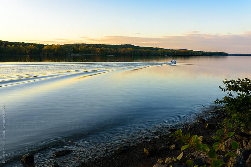 motorboats enjoying sunset on the Hudson river by Deirdre Malfatto for Stocksy United