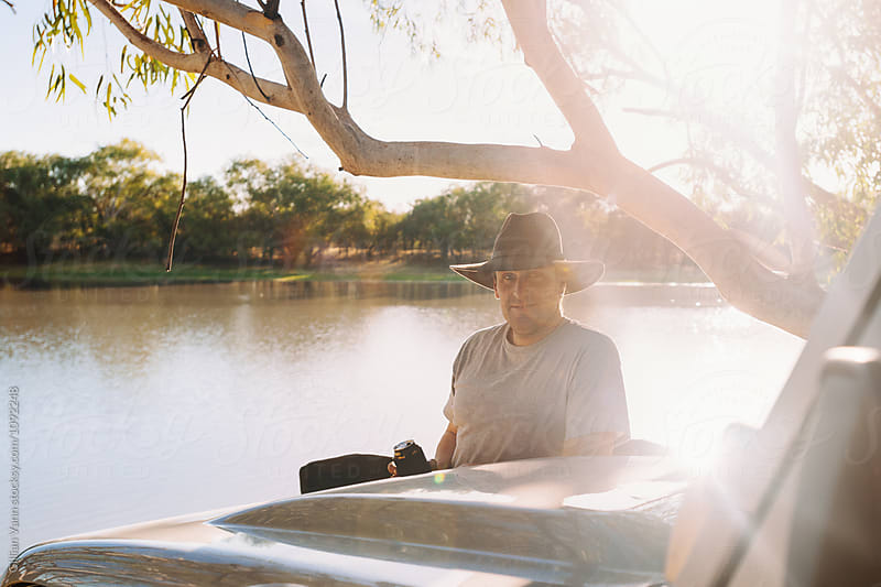 man wearing Akubra hat leaning on the bonnet of his 4x4, holding a can of beer in a stubby by Gillian Vann for Stocksy United