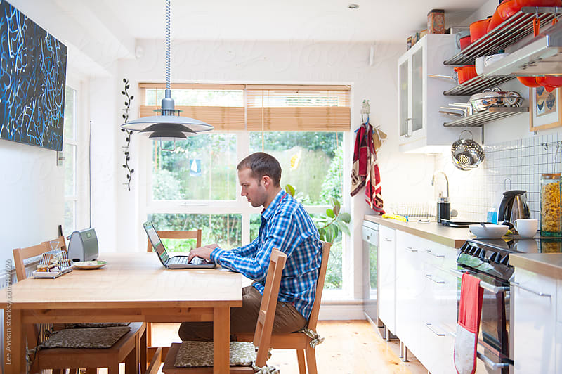 man working at a laptop in the kitchen by Lee Avison for Stocksy United