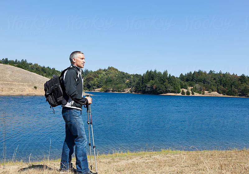 Mature hiker on lake's edge by Tanya Constantine for Stocksy United
