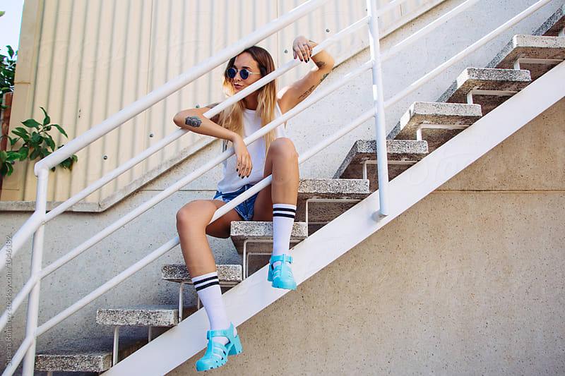 Portrait of stylish woman sitting on stairs by Susana Ramírez for Stocksy United