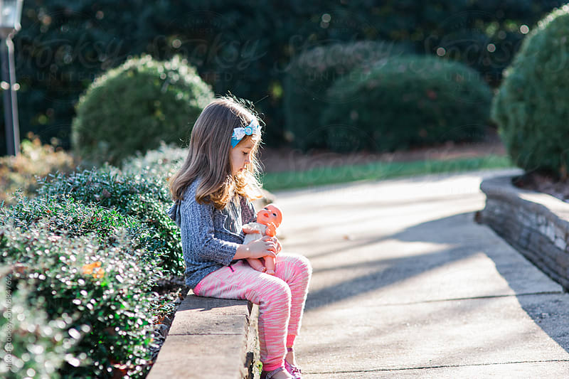 Cute young girl sitting outside with her baby doll by Jakob for Stocksy United