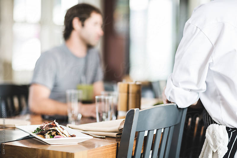 Food on a restaurant table with blurred customer and chef by Lior + Lone for Stocksy United