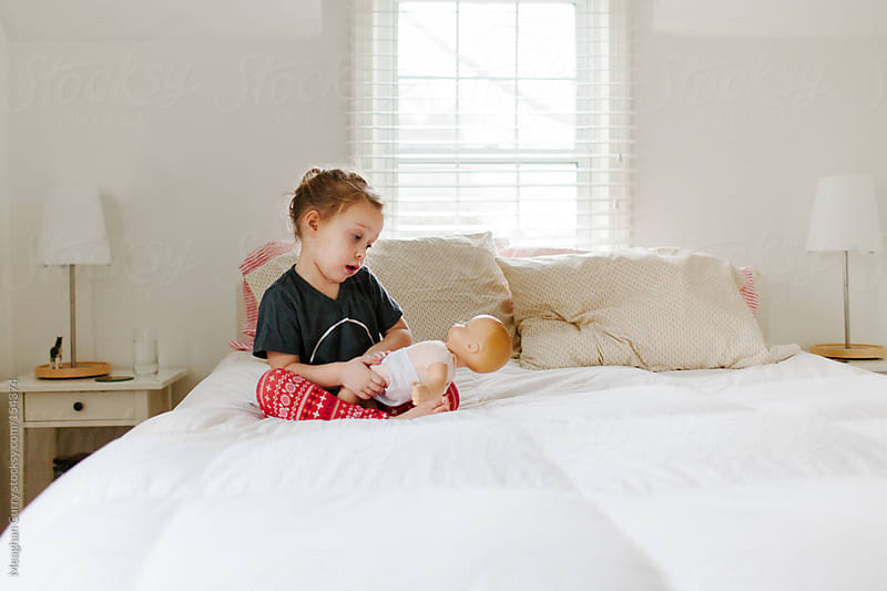 little girl playing with a doll sitting on a bed by Meaghan Curry for Stocksy United