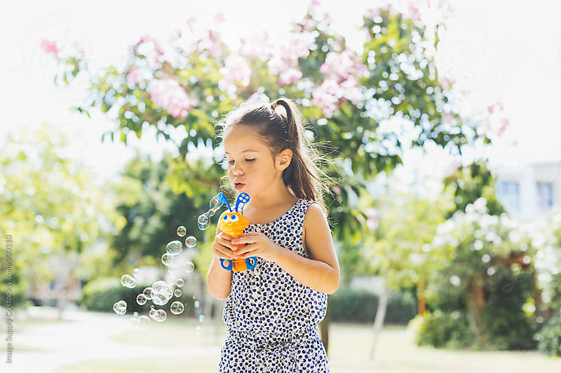 Young toddler girl in park blowing bubbles in the sun by Image Supply Co for Stocksy United