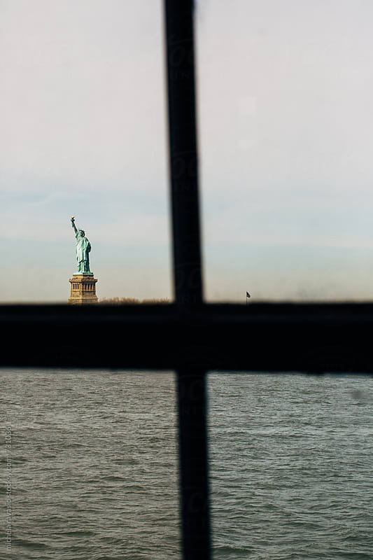 Statue of Liberty from the window of the ferry by michela ravasio for Stocksy United