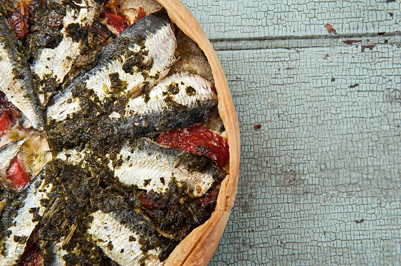 sardine quiche, top down view, on rustic blue tabletop by Gillian Vann for Stocksy United