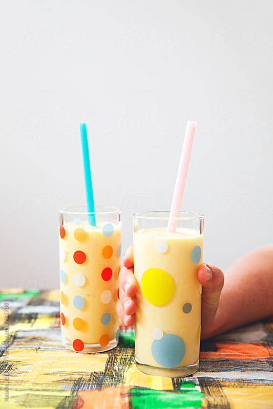 Two glasses of mango lassi sitting on a table with a hand holding a glass by Natalie JEFFCOTT for Stocksy United