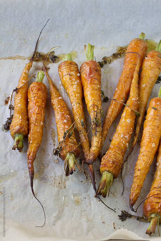 Roasted carrots with thyme on baking paper by Noemi Hauser for Stocksy United