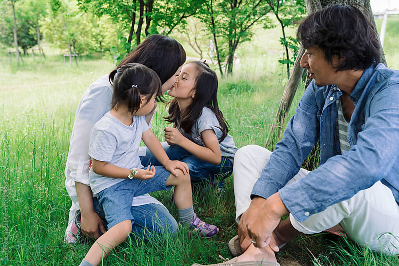 Japanese family together in a park in Japan by Juri Pozzi for Stocksy United