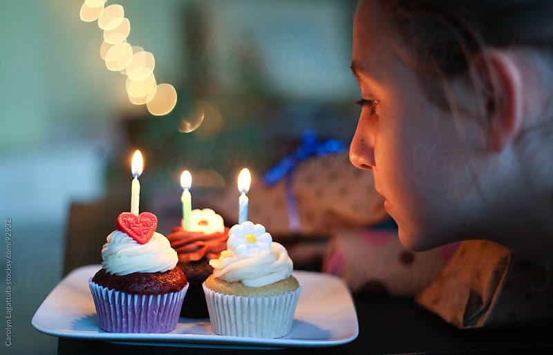 Young girl looking at her birthday cupcakes by Carolyn Lagattuta for Stocksy United