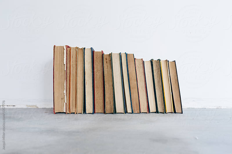Vintage books on cement floor by Jacqui Miller for Stocksy United