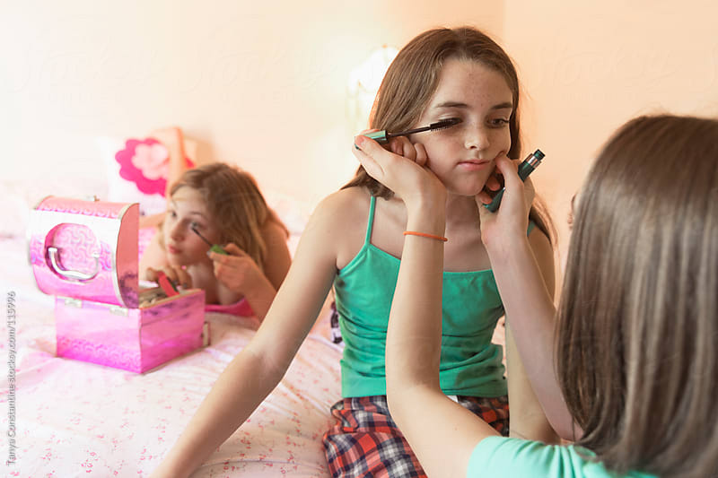 three tween girls putting on make-up in their bedroom by Tanya Constantine for Stocksy United