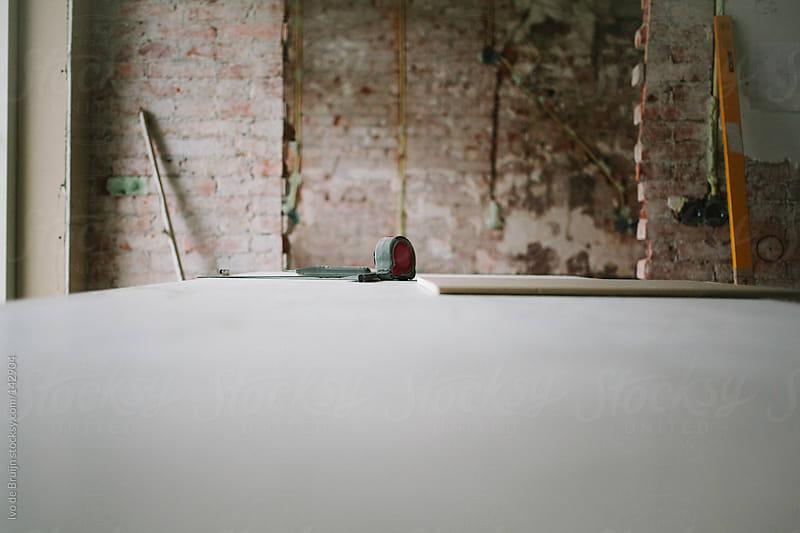 Tapeline lying on plasterboard on a workbench in a home building by Ivo de Bruijn for Stocksy United