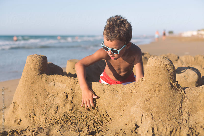 Child making sand castle on the beach   by Dejan Ristovski for Stocksy United