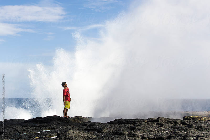Wave splashing on rocks with young man next to it. Blow holes in Samoa by Alejandro Moreno de Carlos for Stocksy United