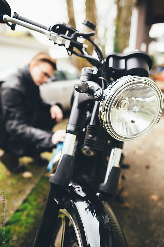 Young Man In Leather Jacket Polishing Black Motorcycle In Driveway by Luke Mattson for Stocksy United