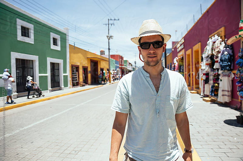 Portrait of young man with sunglasses and straw hat in a colourful street in Mexico by Alejandro Moreno de Carlos for Stocksy United
