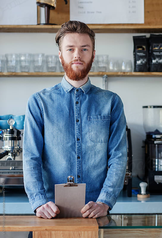 Portrait of young cafe bar owner standing behind the counter by W2 Photography for Stocksy United