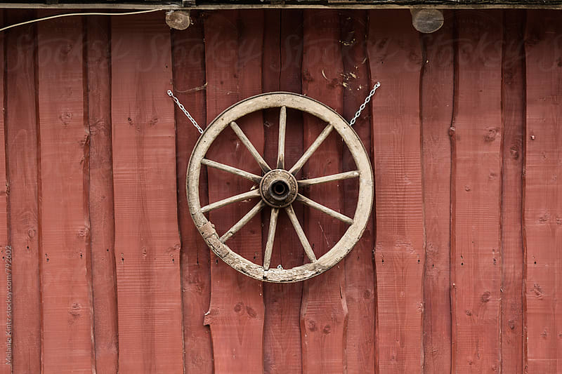 Wooden wheel hanging on a red barn wall by Melanie Kintz for Stocksy United