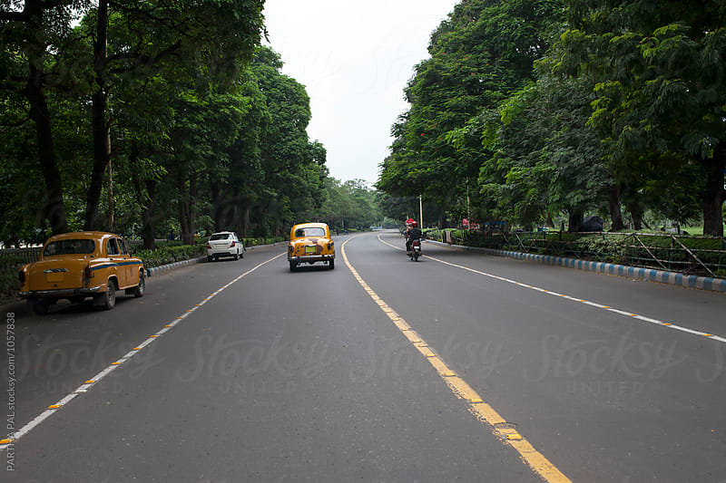 Street view with yellow taxi on road by PARTHA PAL for Stocksy United