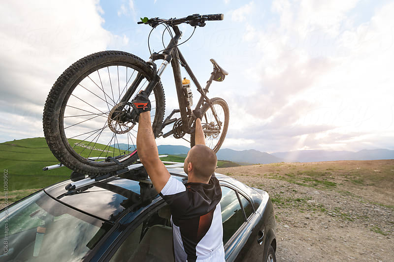 Man lifting bicycle on roof rack by RG&B Images for Stocksy United