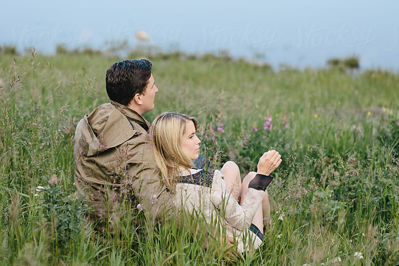 A young couple resting in tall grass looking out into the water by Ania Boniecka for Stocksy United