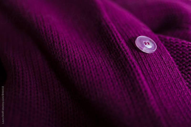 Detail of button on vibrant purple woolen sweater by Laura Stolfi for Stocksy United