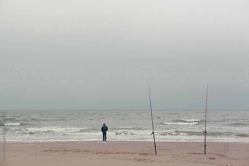 Boy staring at the ocean with two fishing poles in the sand on the beach by Cindy Prins for Stocksy United