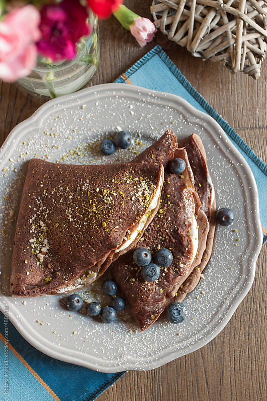 Chocolate crepes with creamy filling and blueberries by Nataša Mandić for Stocksy United