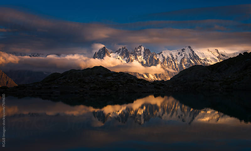 Beautiful sunset over the mountains reflecting in the lake by RG&B Images for Stocksy United