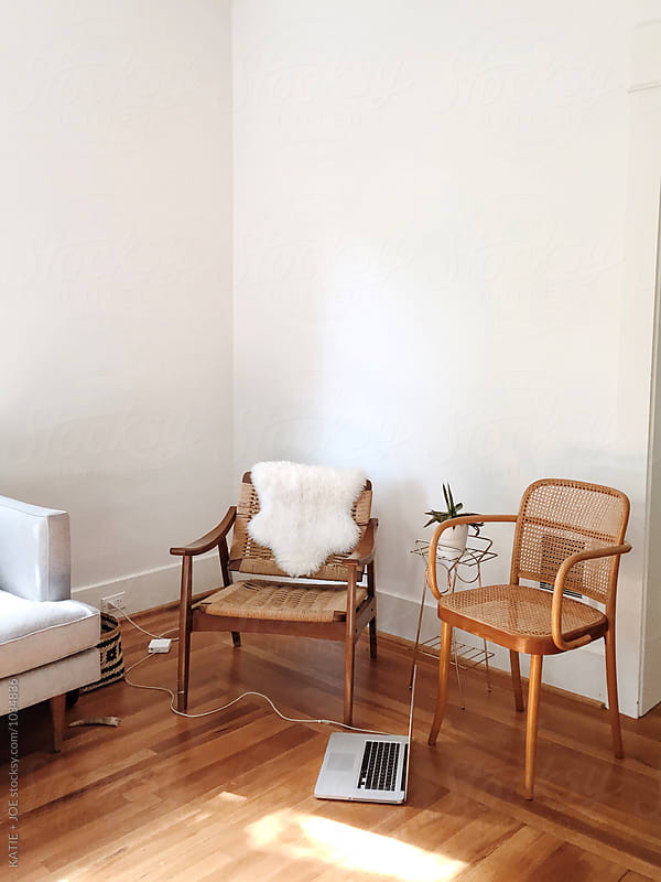 corner of a house with two chairs and a laptop by KATIE + JOE for Stocksy United