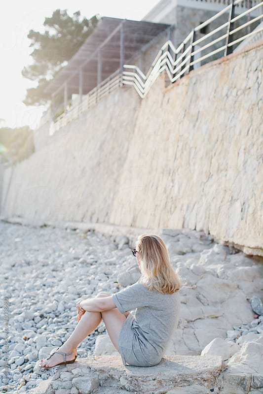 Single adult female sitting on rocks near wall by Amir Kaljikovic for Stocksy United