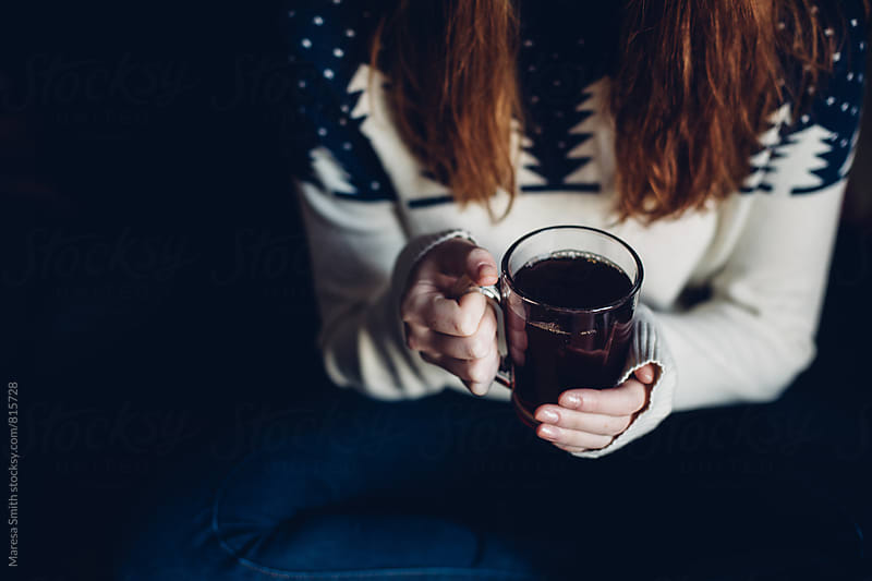 Close up of women's hands holding a mug of tea or coffee, she wears a festive jumper by Maresa Smith for Stocksy United