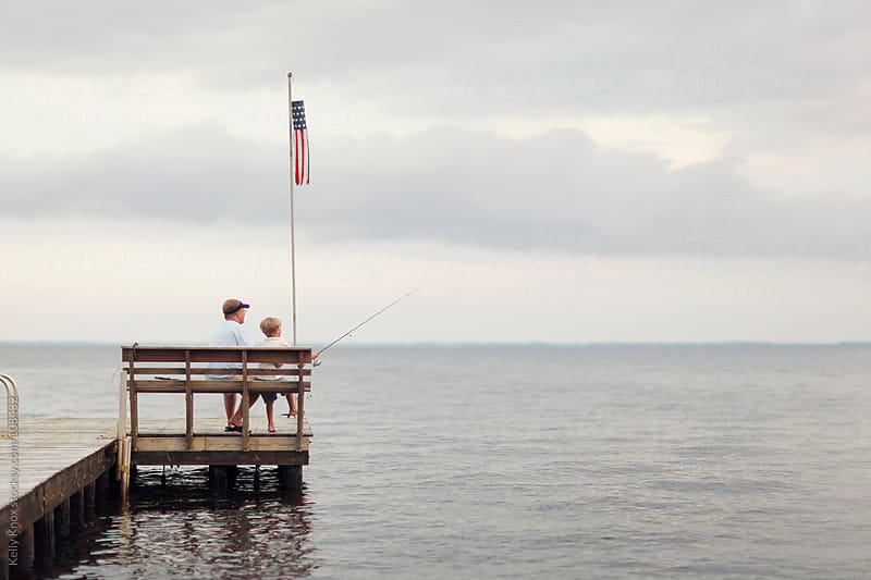 father and son fish off the end of a pier by Kelly Knox for Stocksy United